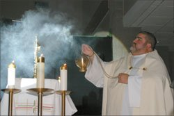 Priest incenses the altar